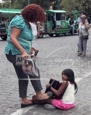 Eικόνες που σοκάρουν: Ιδιοκτήτρια καταστήματος στον πεζόδρομο της Ακρόπολης κλοτσάει παιδί που παίζει ακορντεόν και ζητιανεύει - Φωτογραφία 2