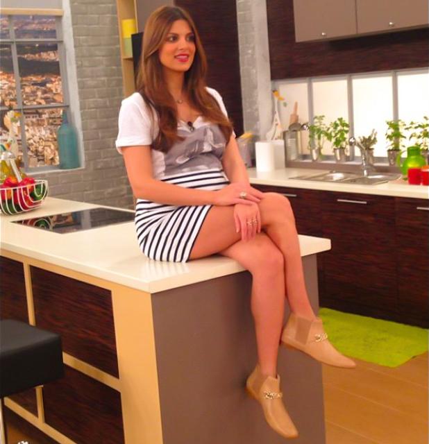Έγκυος παρουσιάστρια κάνει σταυροπόδι πάνω στον πάγκο της κουζίνας - Φωτογραφία 2